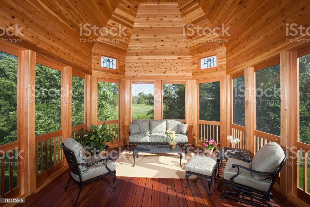Three season porch with pine ceiling and backyard view. royalty-free stock photo