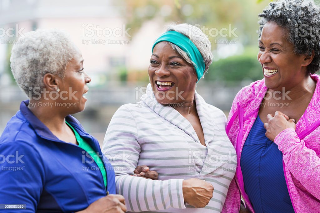 Three senior black women laughing together outdoors stock photo