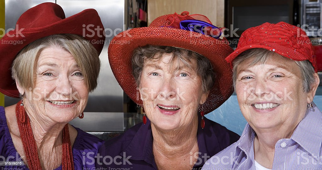 Three Senior Women Wearing Red Hats stock photo