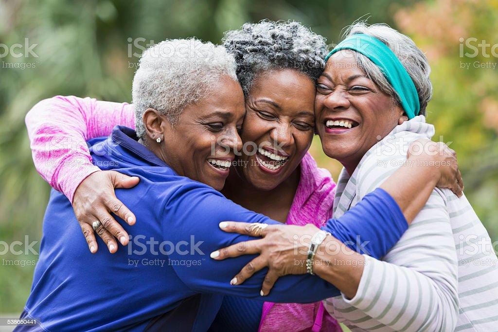 Three seniors hugging stock photo