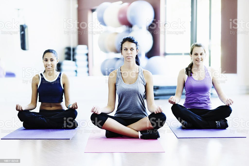 Three serenely smiling young women enjoy a Yoga class stock photo