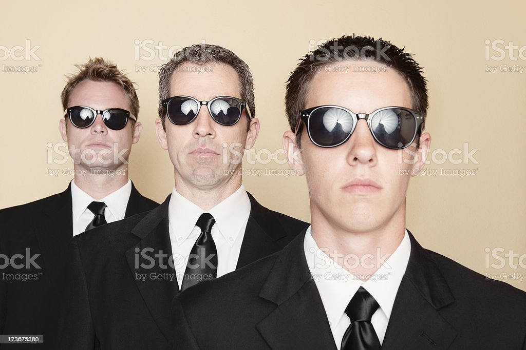 Three Serious American Men in Black Suits Standing Together stock photo