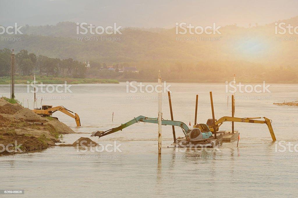 Three shovel buckets on pontoon are dredging waterway. stock photo