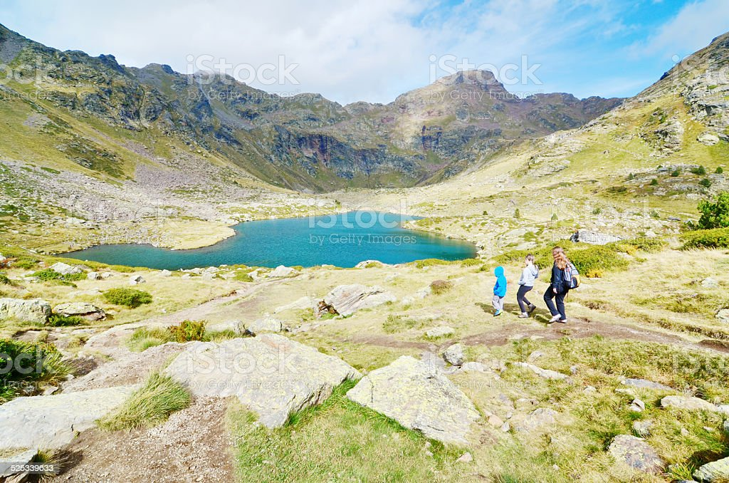Three siblings hiking to Estany Primer in Tristaina, Andorra stock photo