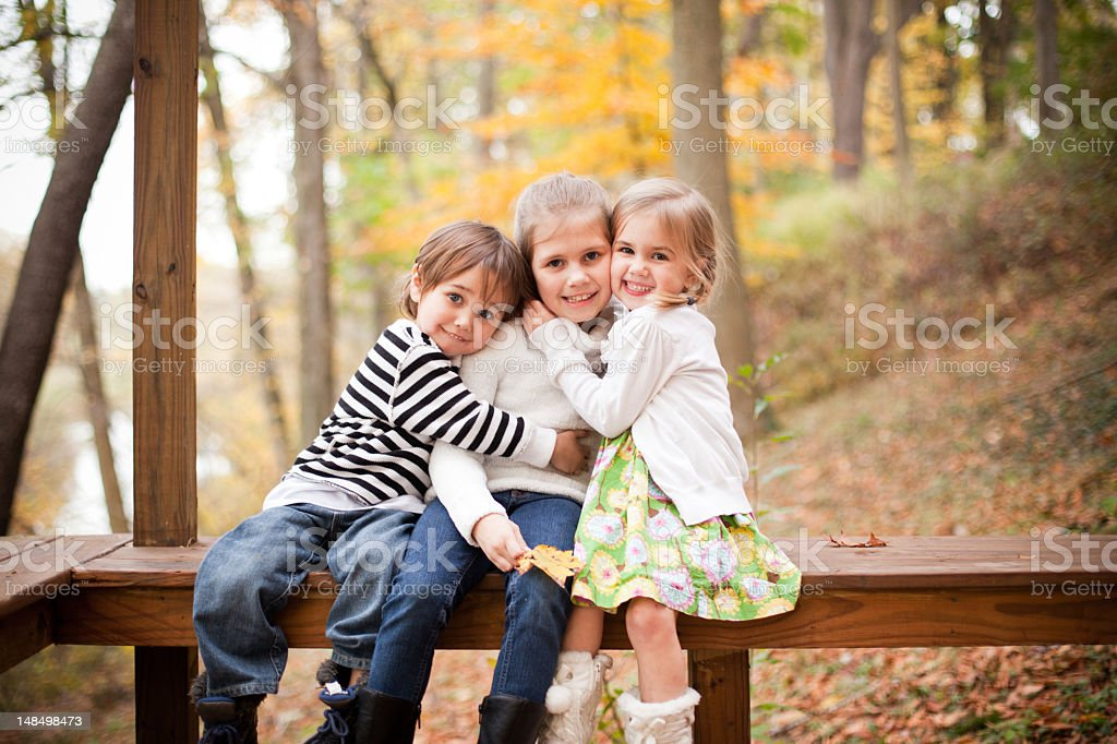 Three siblings posing for a picture in an Autumn forest stock photo