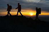 Three silhouettes of hikers climbing at sunset