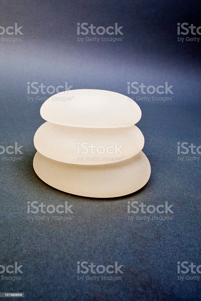 Three silicone breast implants on a background stock photo