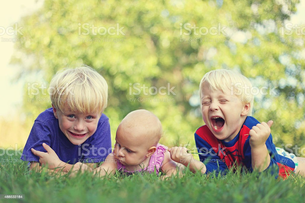 Three silly Children Relaxing Outside stock photo