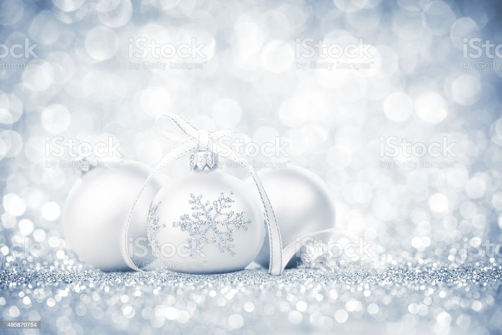 Three silver bauble with snowflake decoration and ribbon on glitter stock photo