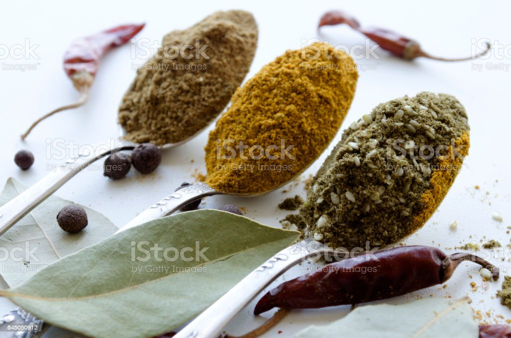 three silver teaspoons with different spices stock photo