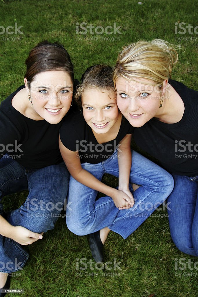 Three Sisters Sitting in the Grass royalty-free stock photo