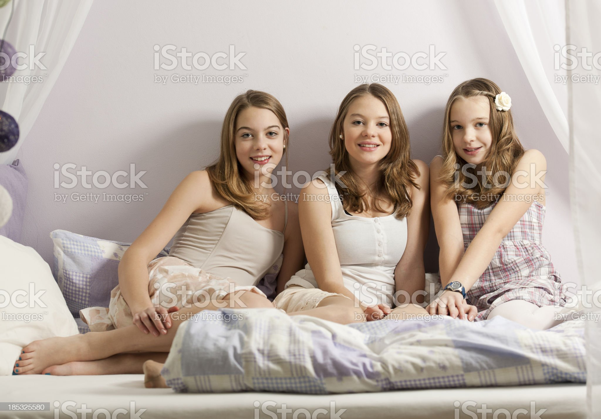 Three sisters sitting on bed royalty-free stock photo