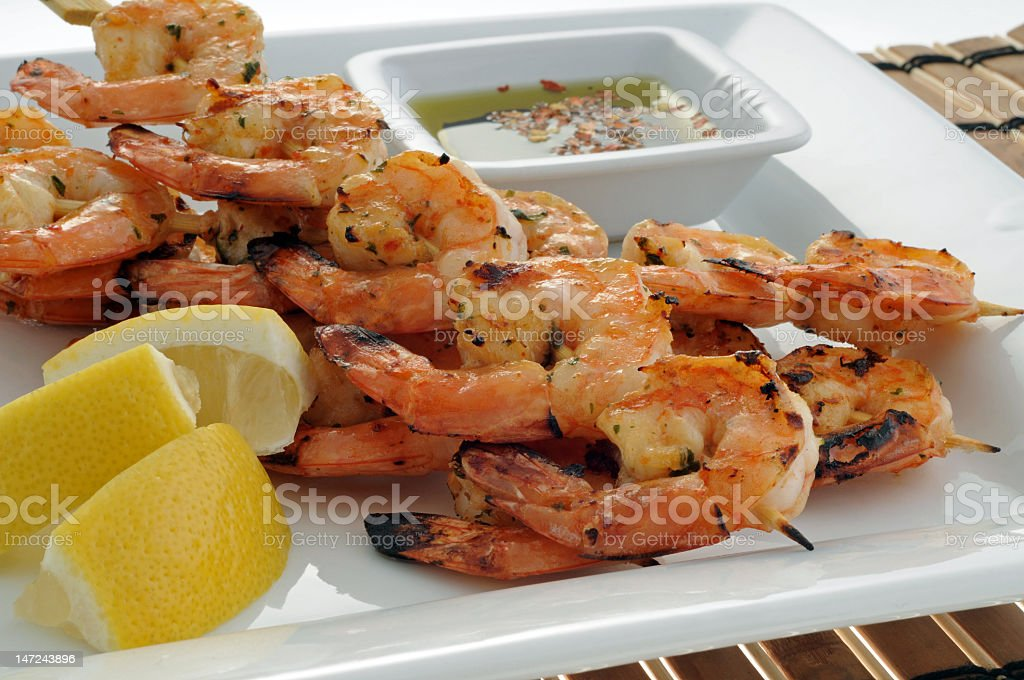 Three skewers of shrimp on a white plate with a lemon slice royalty-free stock photo