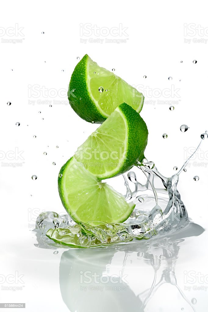 Three slices of lime falling into water stock photo