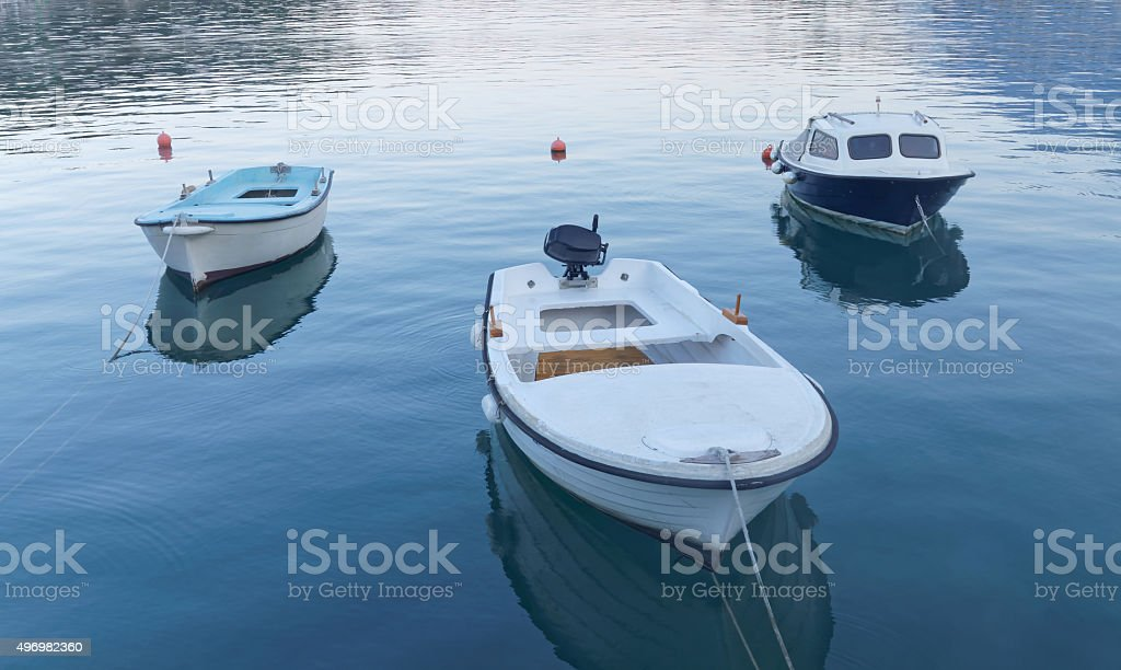 Three small fishing boat in calm water stock photo