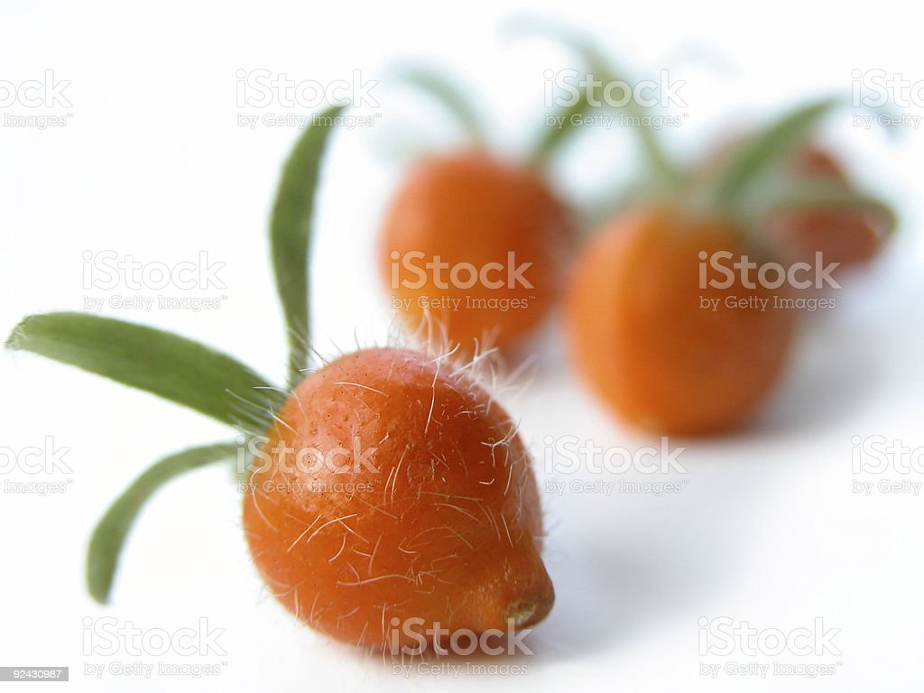 Three Small Orange Berries with Green Tops on White Background royalty-free stock photo