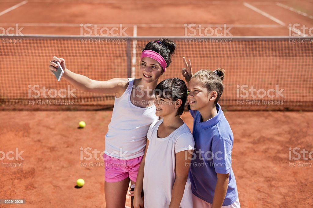 Three small tennis player taking selfie with cell phone. stock photo