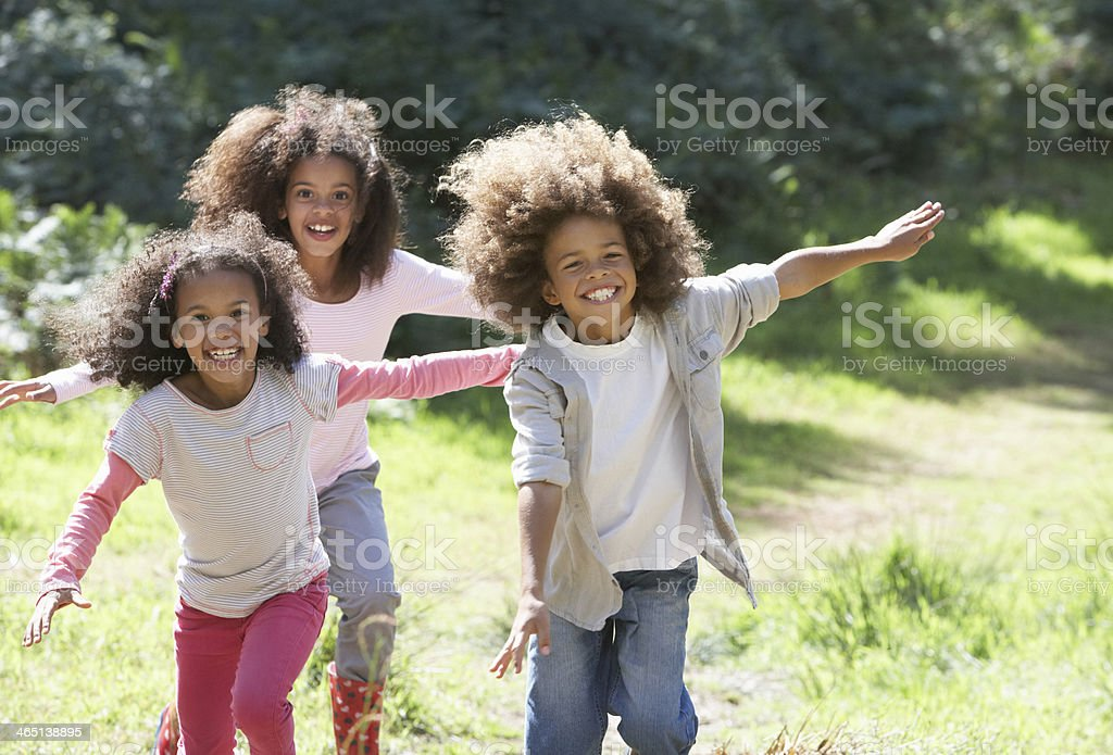 Three Smiley kids in the woods running toward the camera stock photo