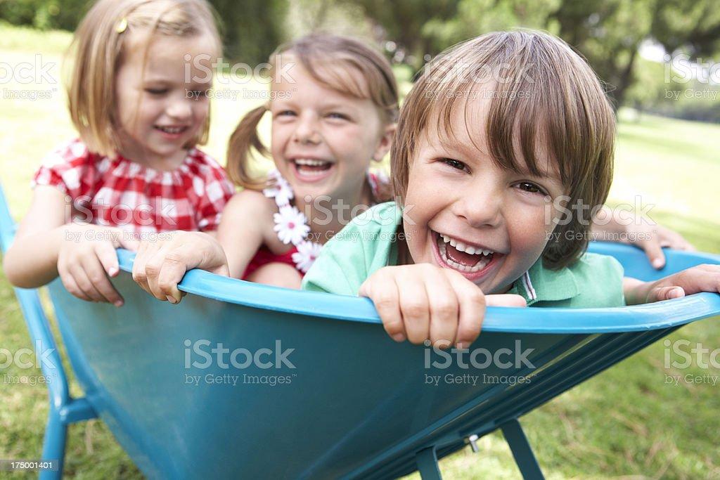Three smiling children sitting in a blue wheelbarrow stock photo