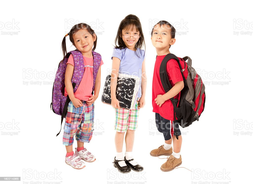 Three smiling children with backpacks and school supplies royalty-free stock photo