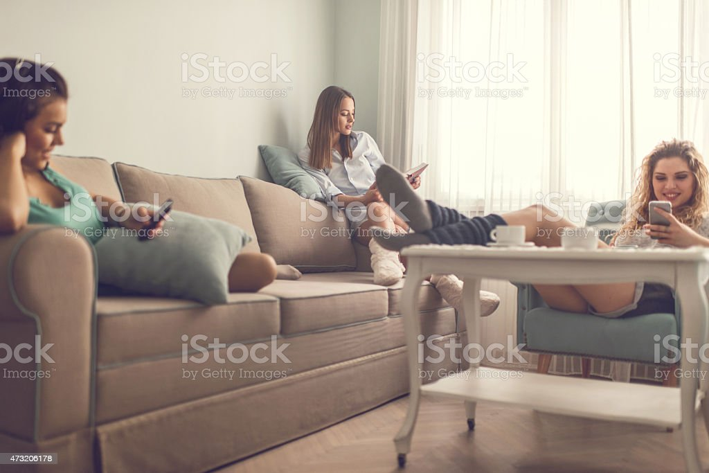 Three smiling female roommates relaxing in the living room. stock photo