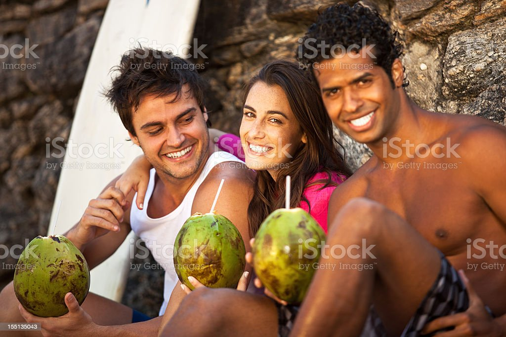 Three smiling friends drinking coconut juice on the beach. royalty-free stock photo