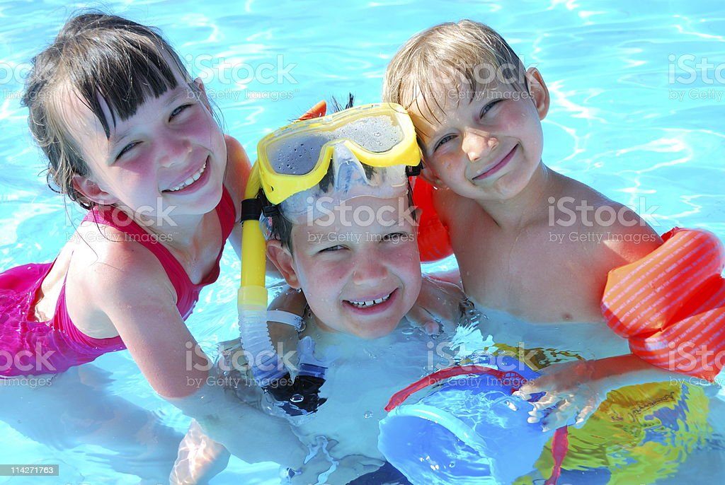 Three smiling kids in a swimming pool with toys stock photo