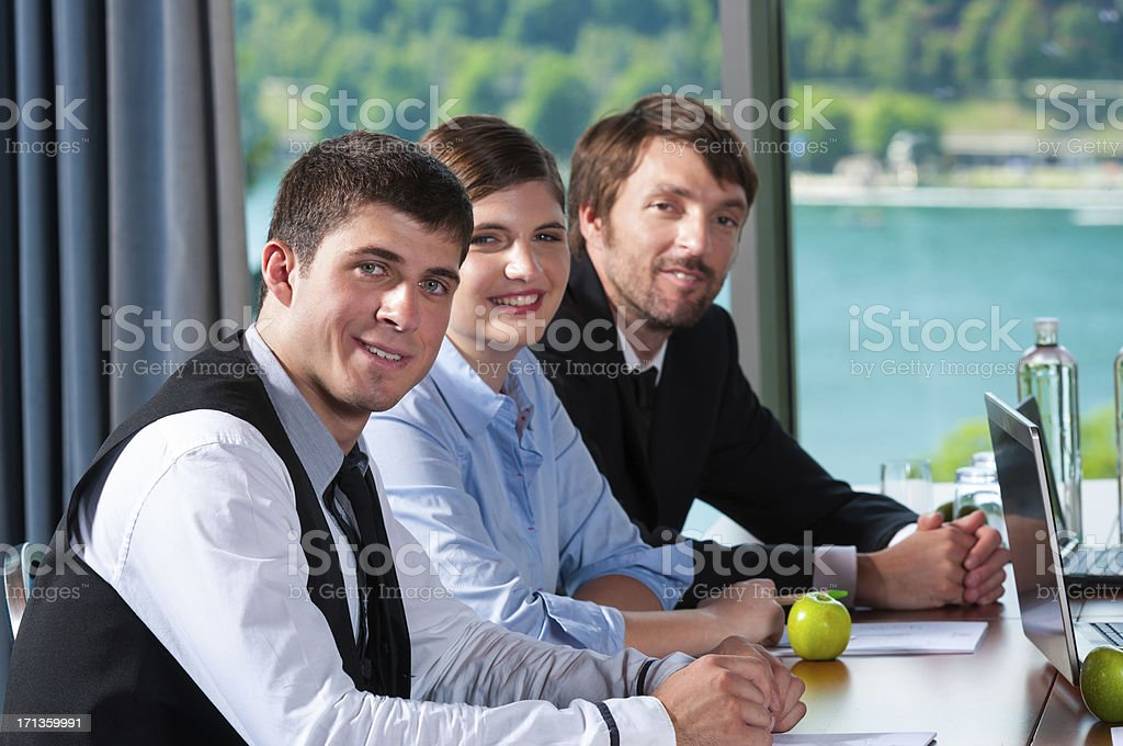 Three smiling people sitting at a table at work. stock photo