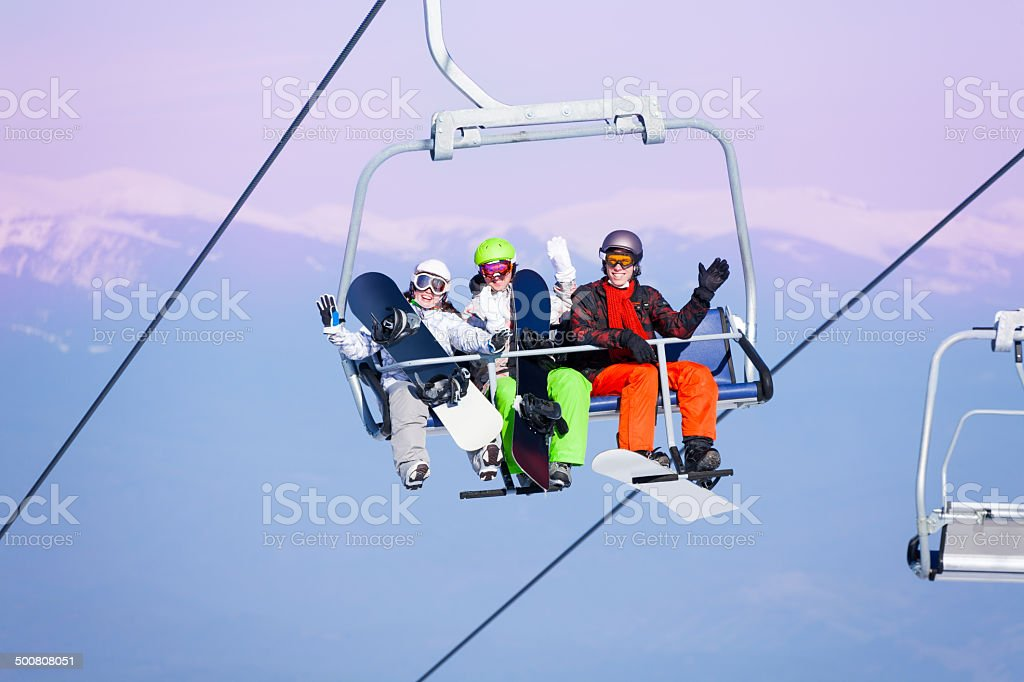 Three smiling snowboarders sitting on ropeway stock photo
