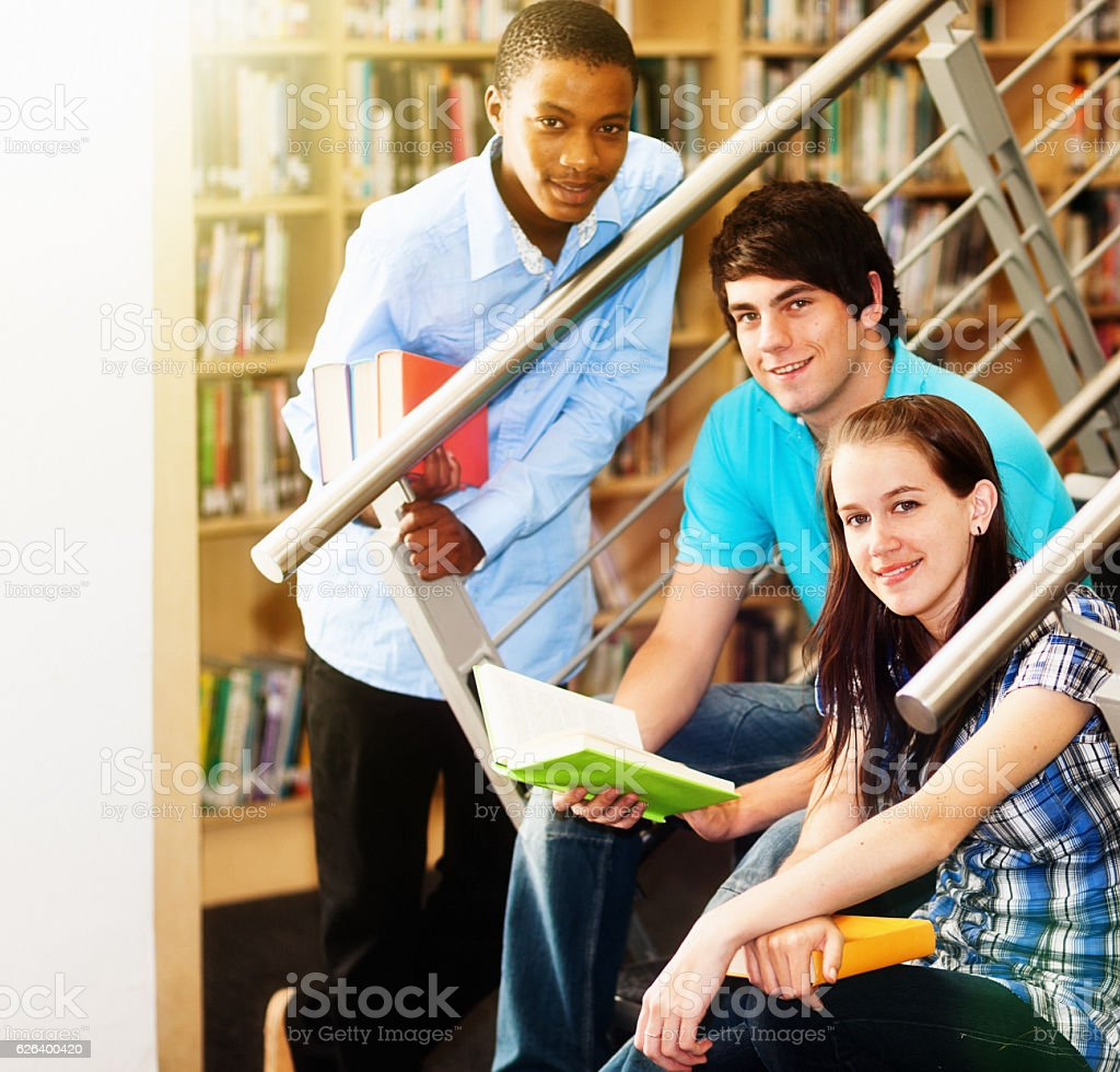Three smiling students sit on library stairs to study together stock photo