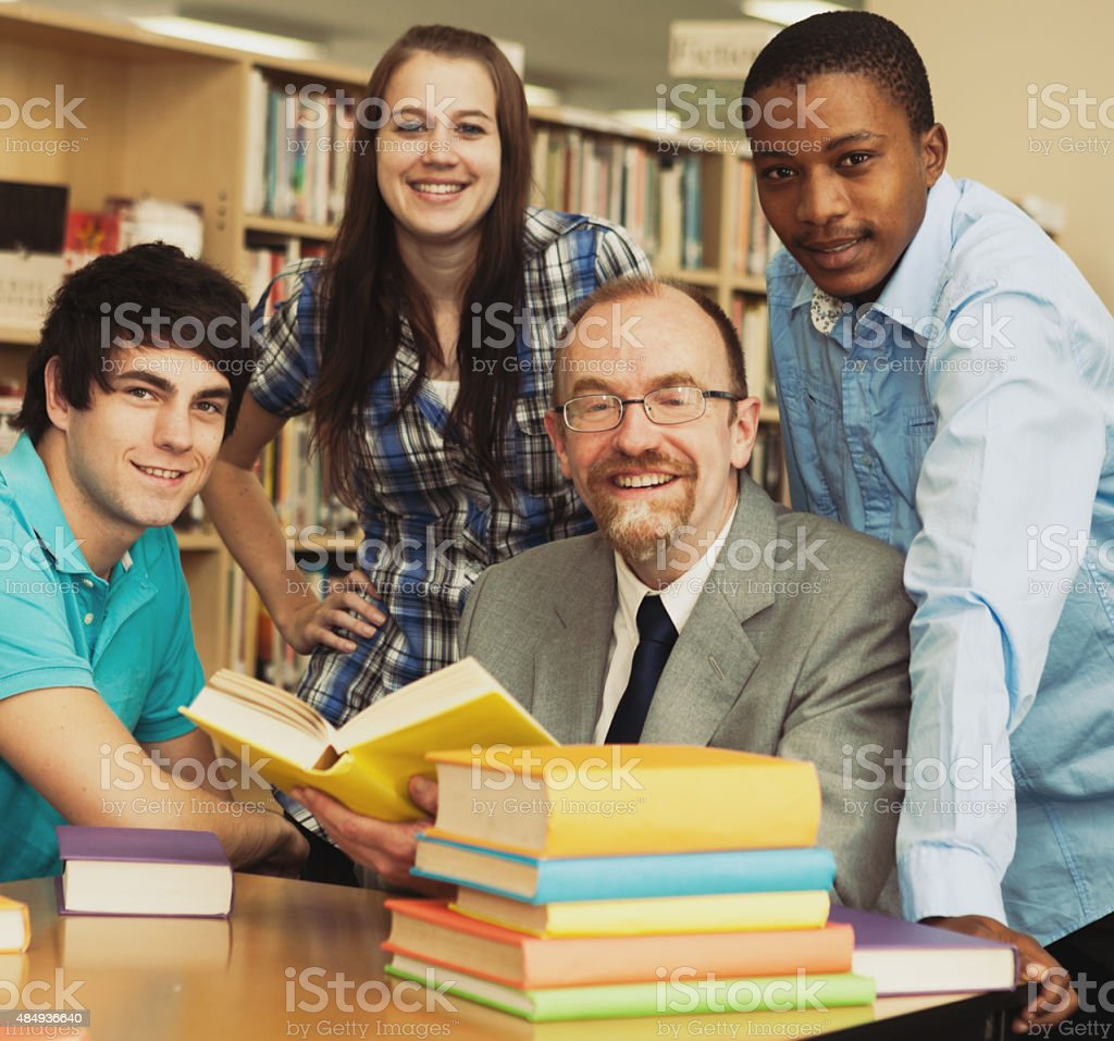 Three smiling students with their friendly teacher in campus library stock photo