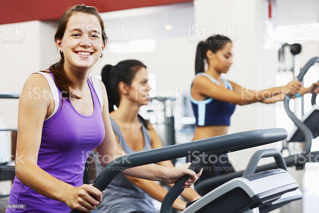 Three smiling women using the equipment in gym stock photo