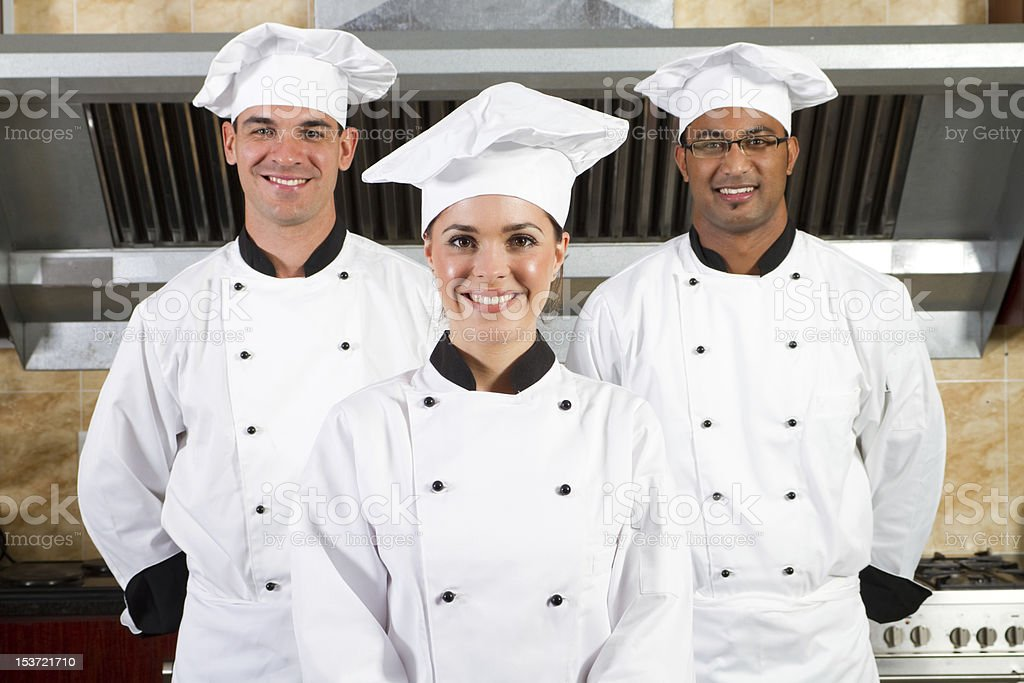 Three smiling young chefs in a large kitchen royalty-free stock photo