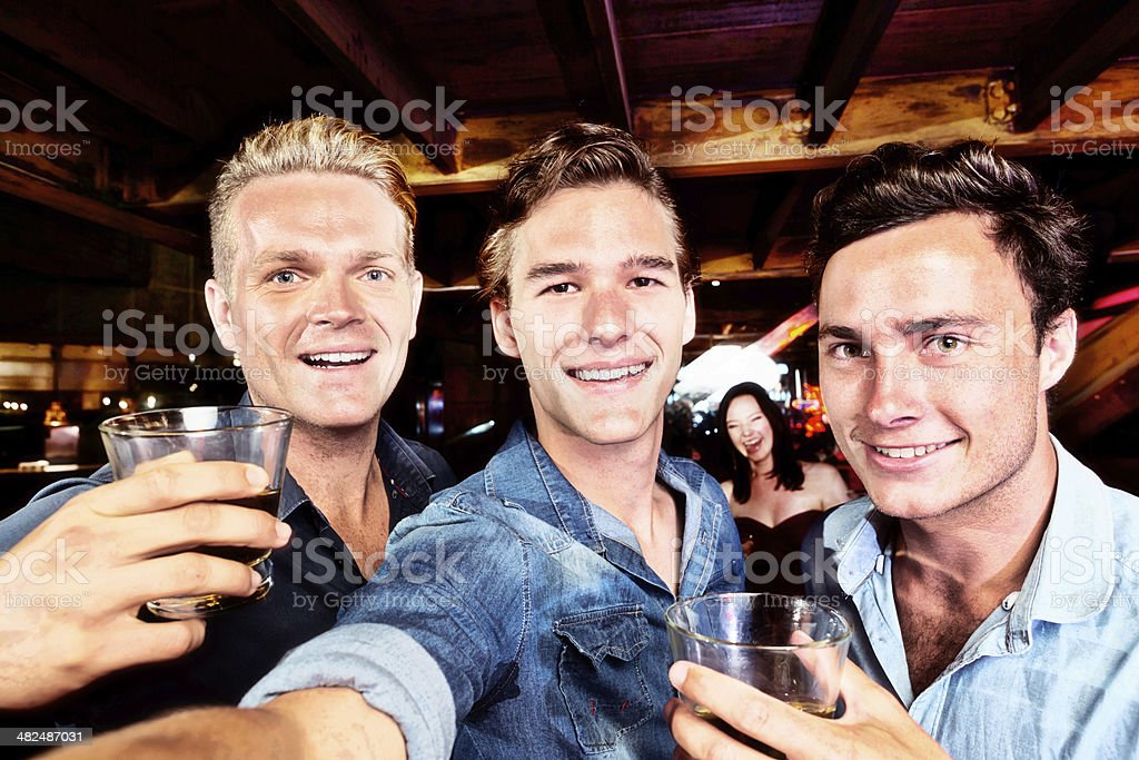 Three smiling young men in bar take a selfie royalty-free stock photo