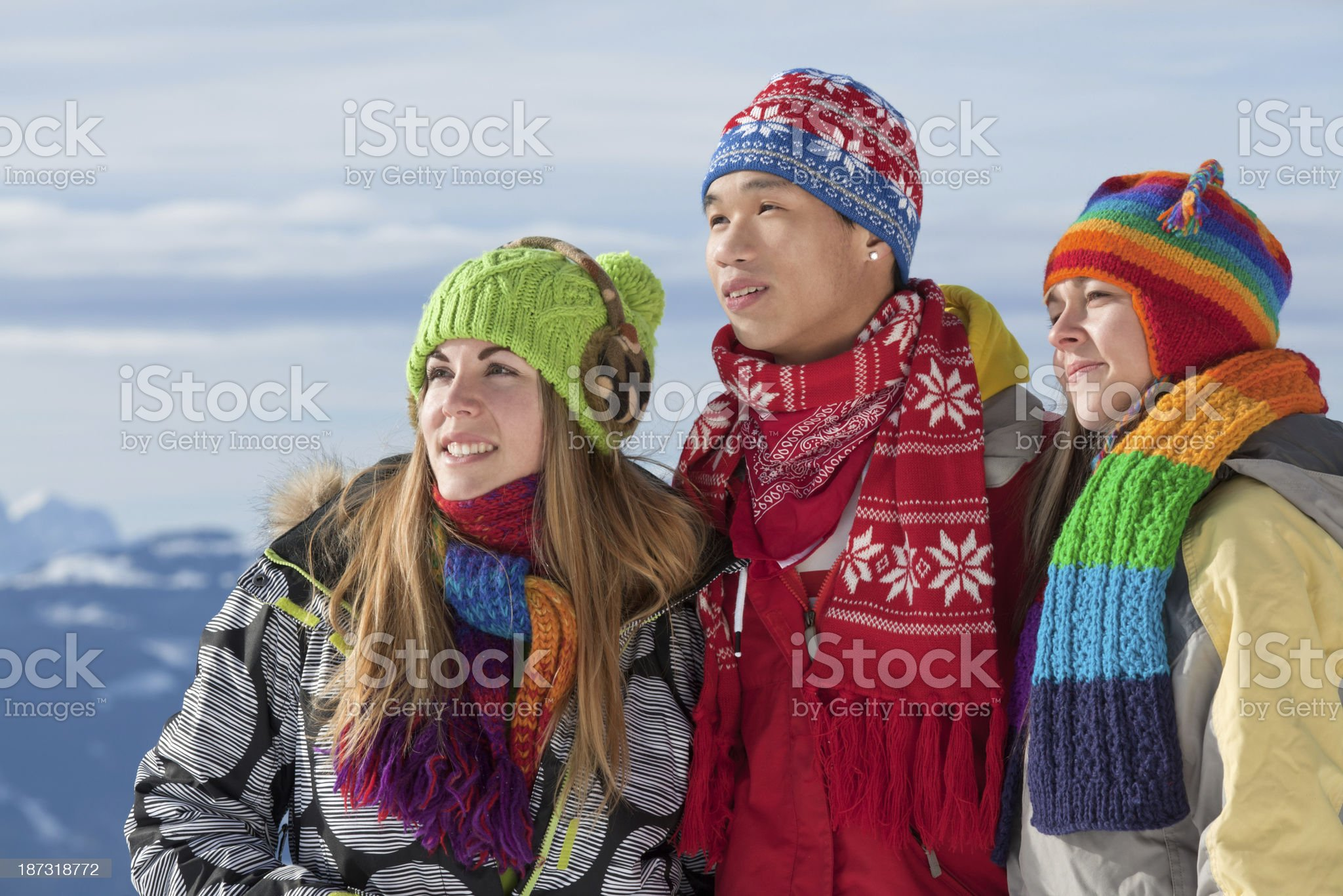 Three smiling young people in winter clothes outdoors royalty-free stock photo