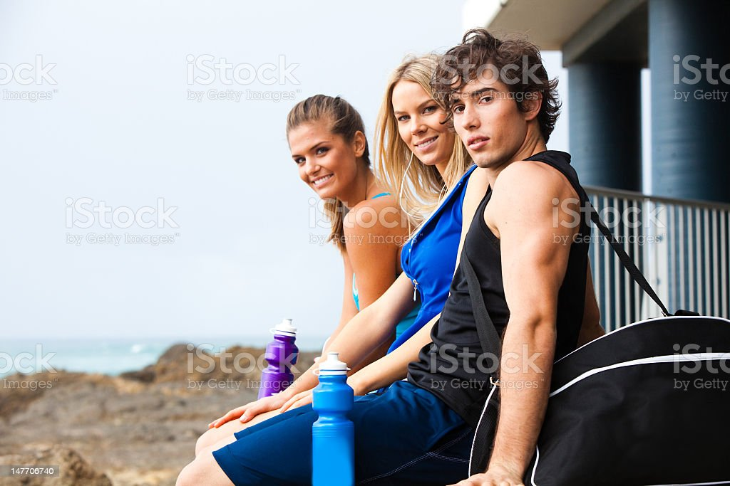 Three smiling young people with water bottles at the beach stock photo