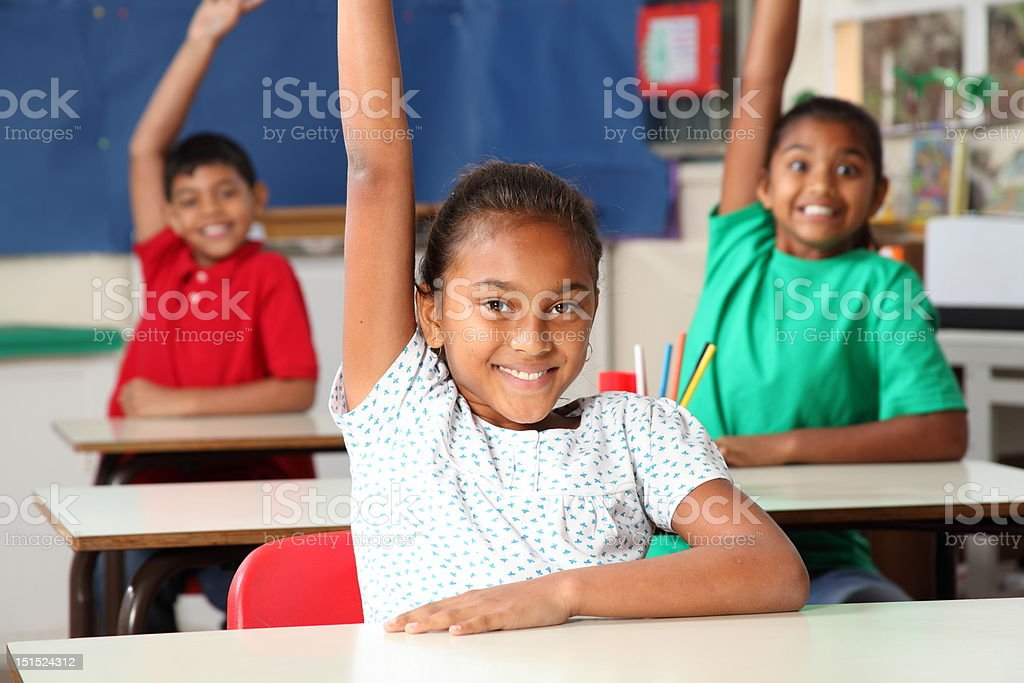 Three smiling young school children arms raised in class royalty-free stock photo