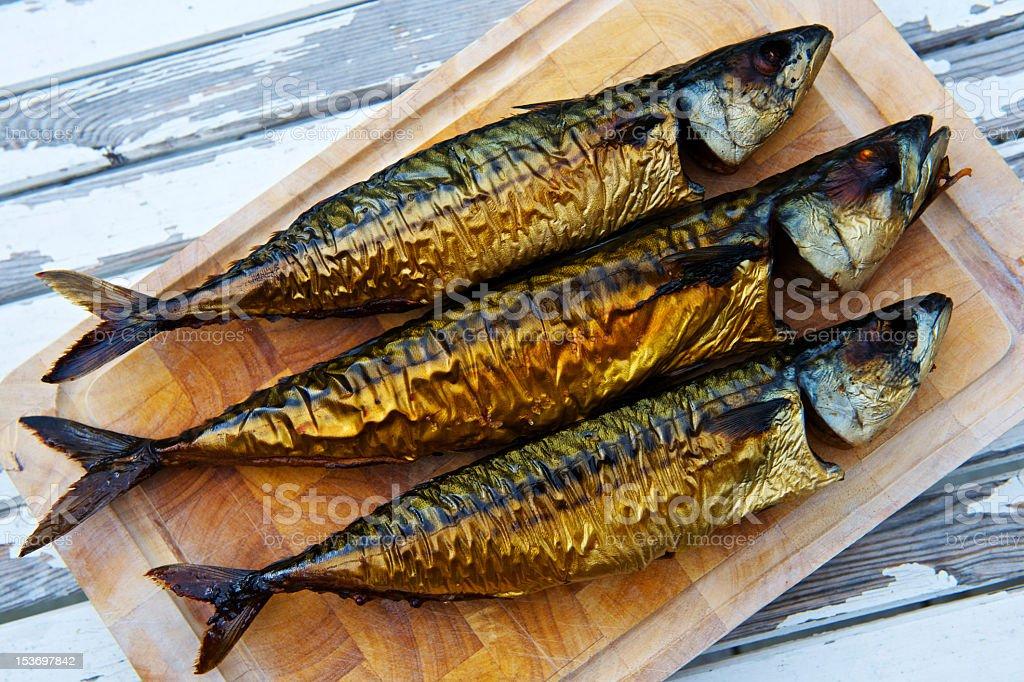 Three smoked mackerel on a wooden board stock photo
