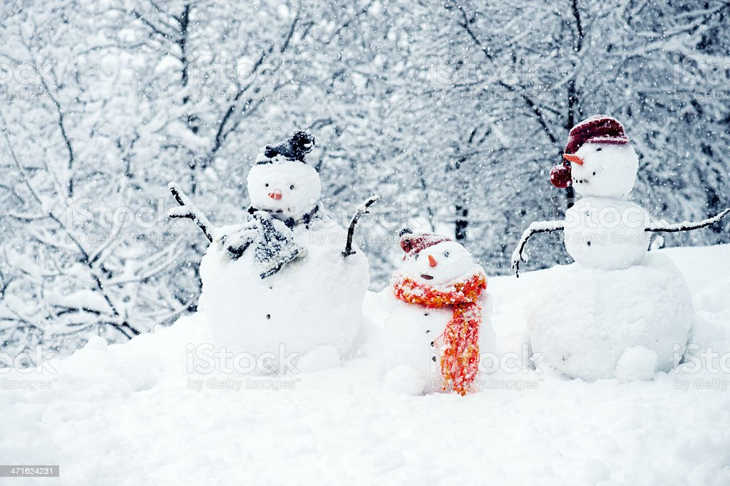Three snowmen with trees in the background stock photo