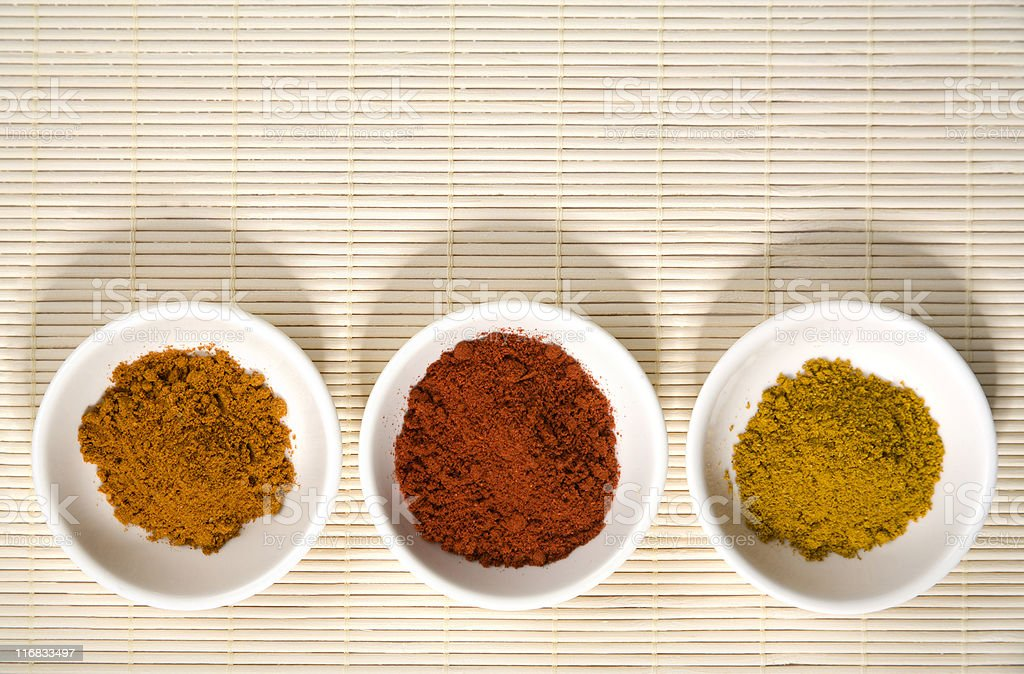 three spices in bowls on straw mat royalty-free stock photo