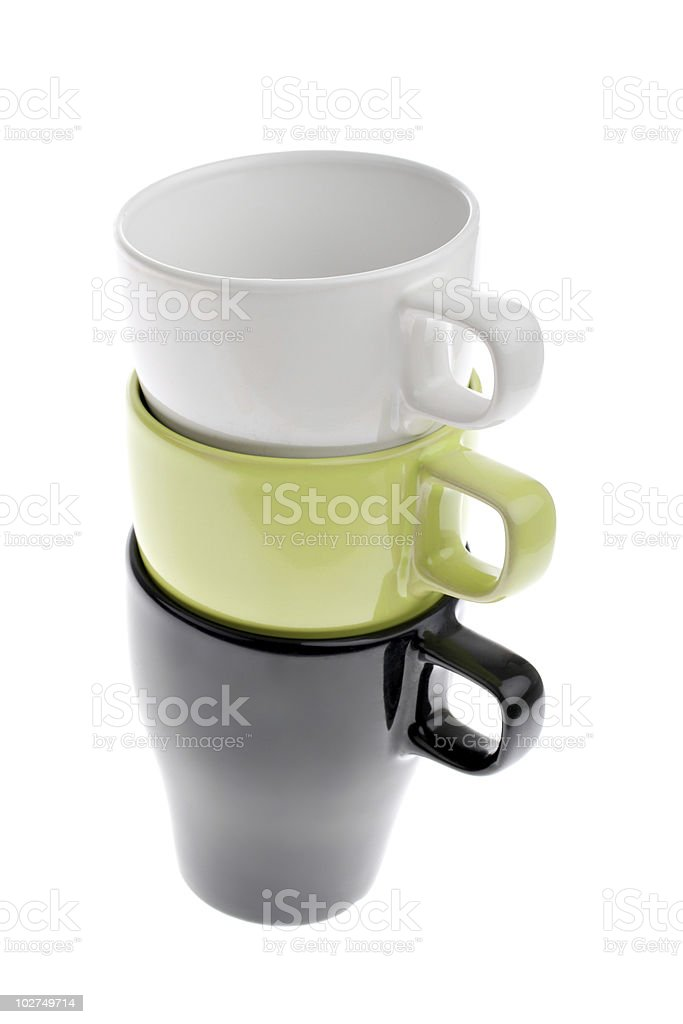 Three stacked white green and black coffee cups isolated stock photo