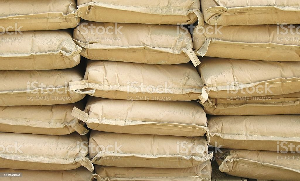 Three stacks of tan cement bags royalty-free stock photo
