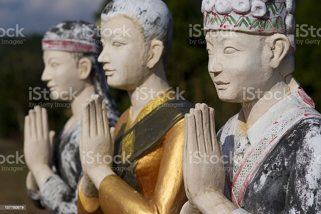 three statues praying outside buddhist temple, laos stock photo