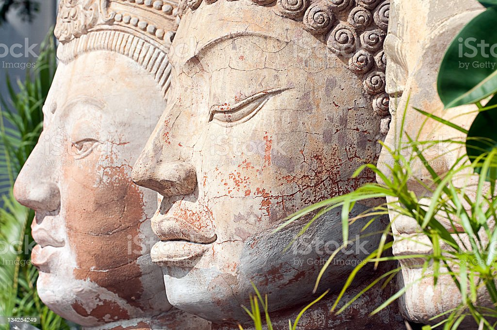 Three stone buddha heads sit beside each other amongst trees royalty-free stock photo