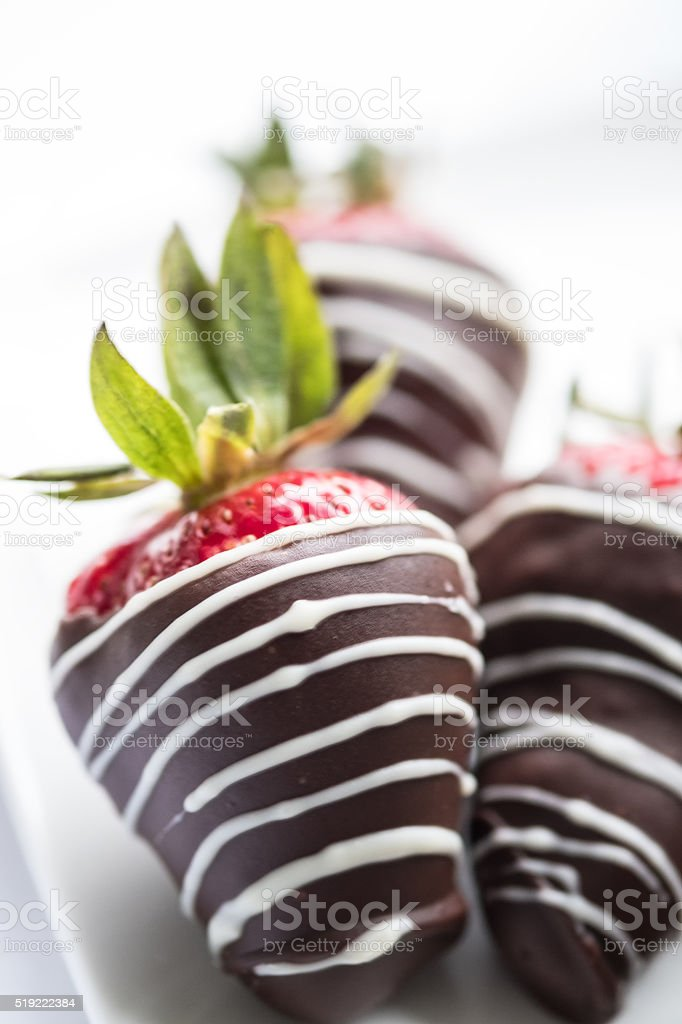 Three Strawberries Dipped in Dark Chocolate with White Chocolate Drizzle stock photo