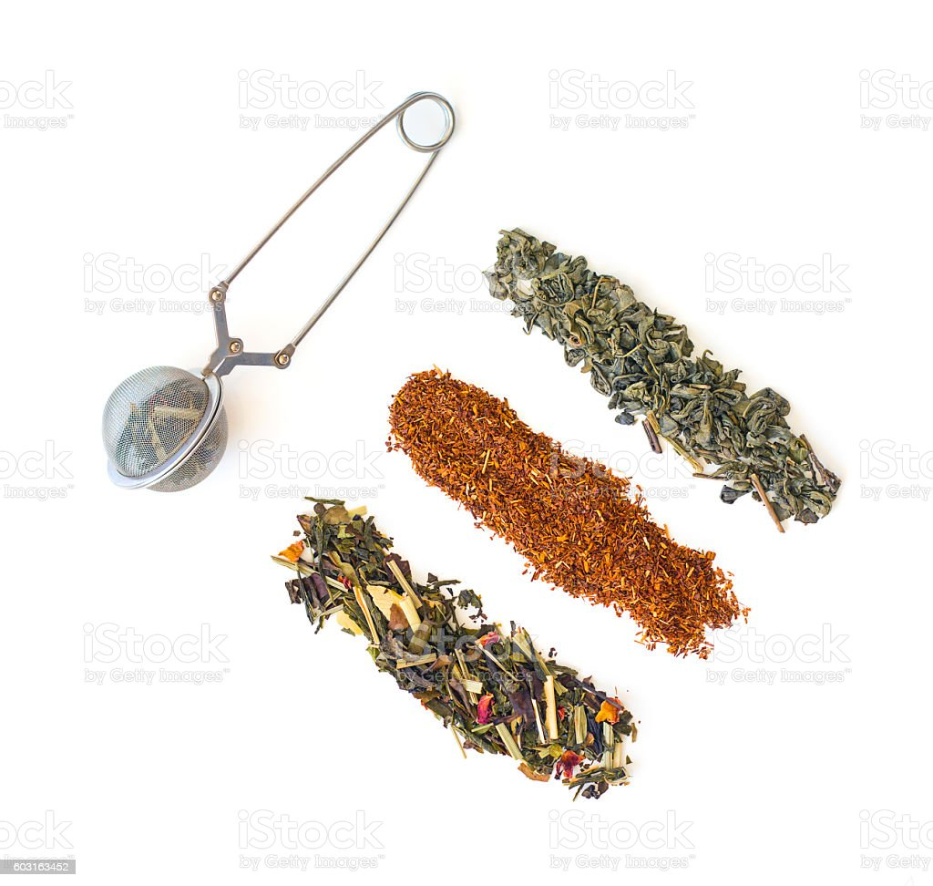 Three strips of Loose leaf tea with filled metal strainer stock photo