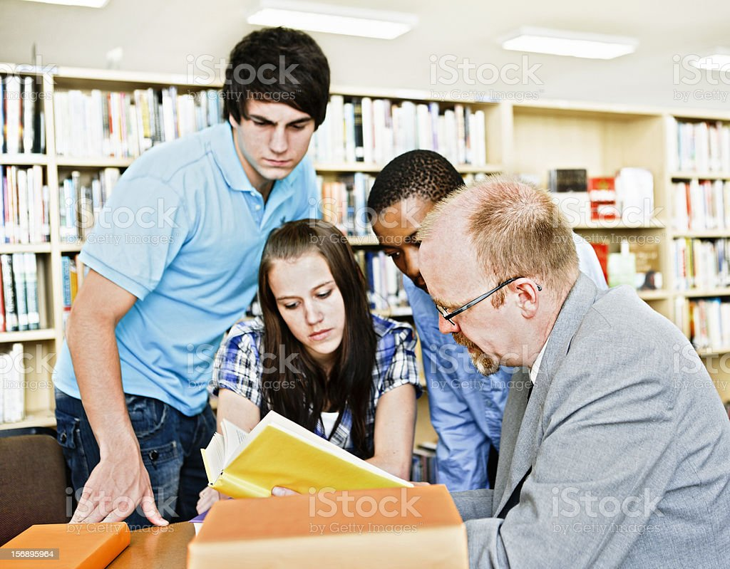 Three students and professor study book together seriously royalty-free stock photo