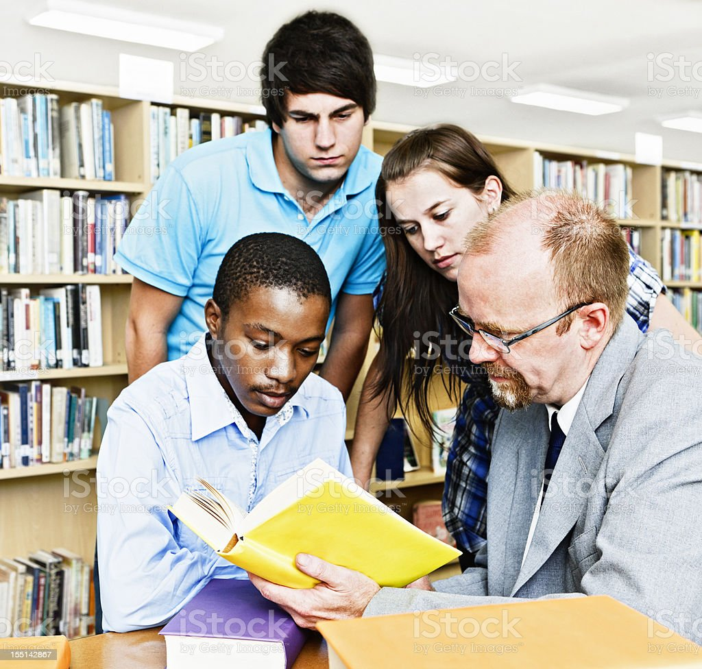 Three students and teacher study a book in campus library royalty-free stock photo