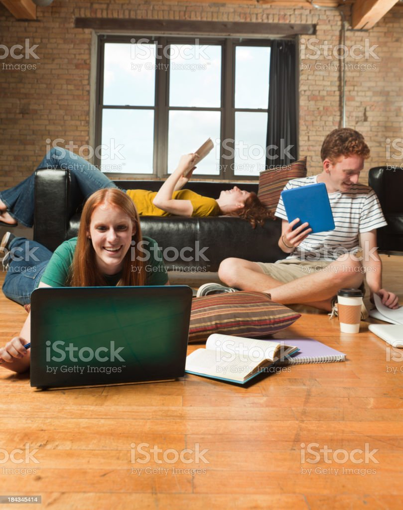 Three students doing homework on hardwood floor royalty-free stock photo
