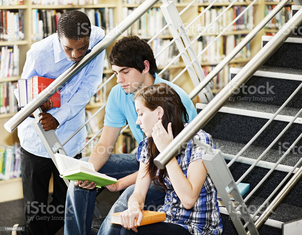Three students gathered at library stairs study a book together royalty-free stock photo